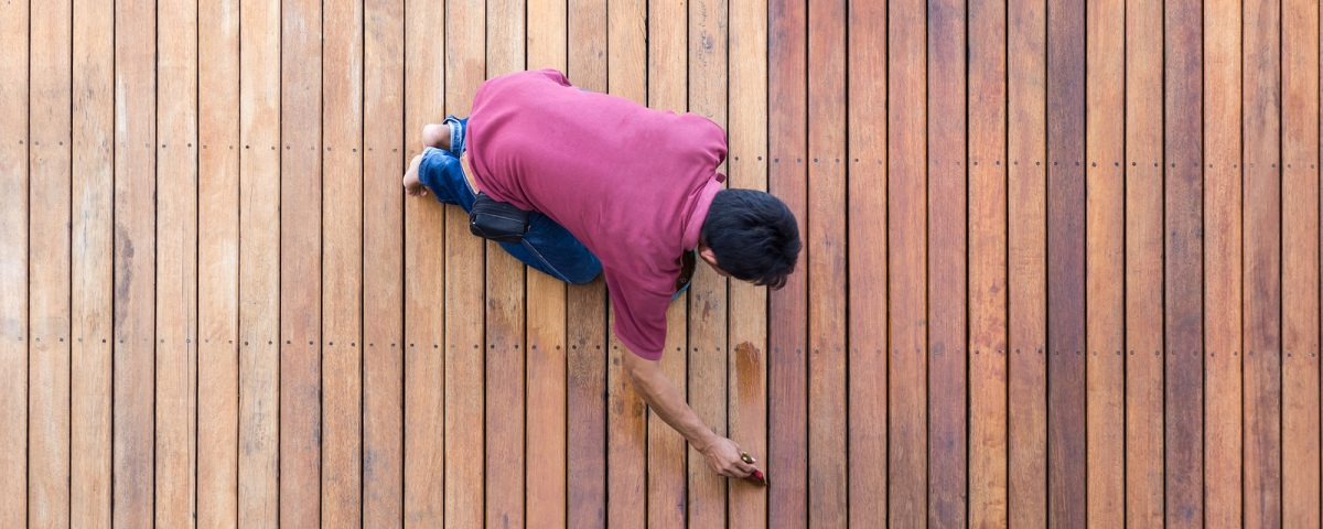 A worker painting exterior wooden pool deck Top view